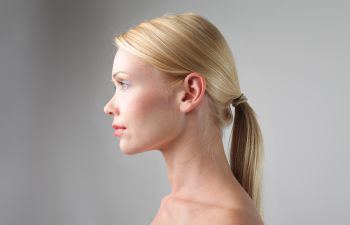 profile of a woman with blond long hair tied at the back of head