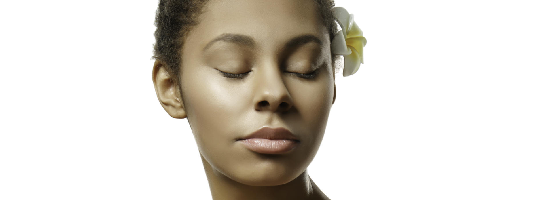 Youthful smooth face of an Afro-American woman with closed eyes and a flower behind her left ear.