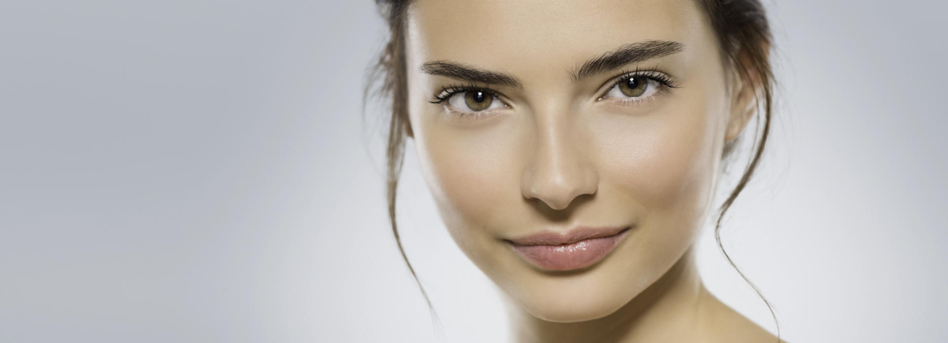 Face of a young-looking woman after facial rejuvenation treatment.