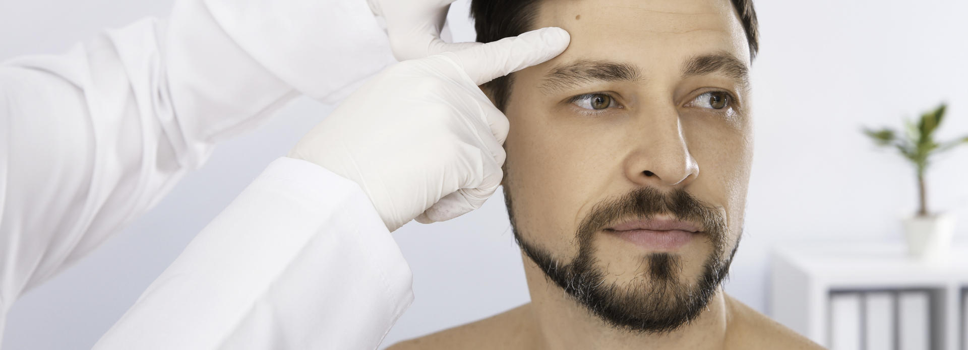 the face of a man with a birthmark being checked by a doctor