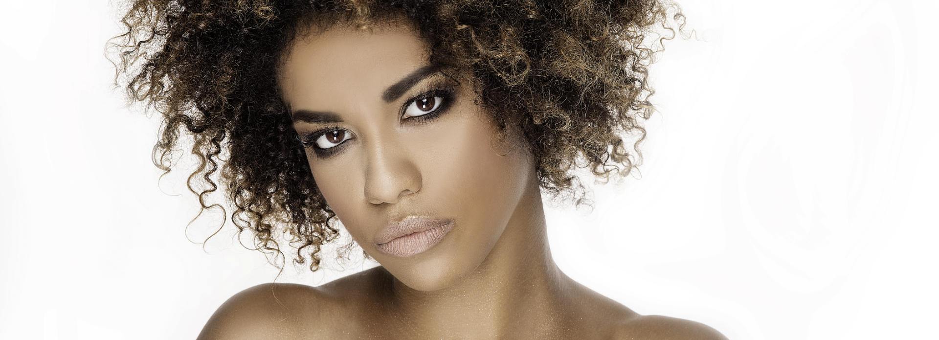 Face of an Afro-American woman with flowless radiant skin after light therapy.