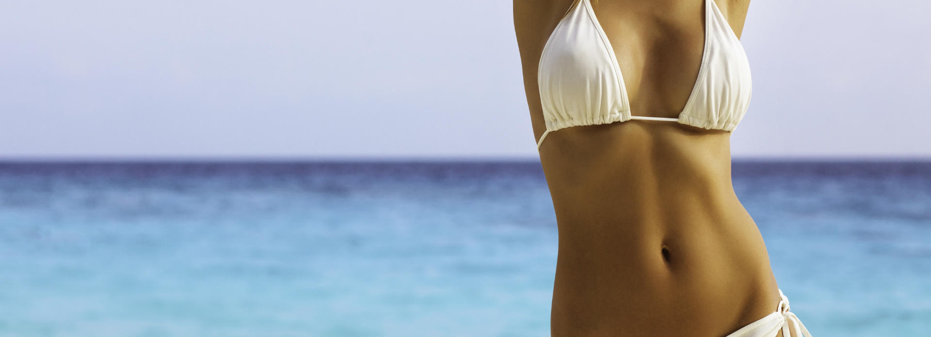 Slim woman after Coolscuplting treatment wearing bikini while on the beach.