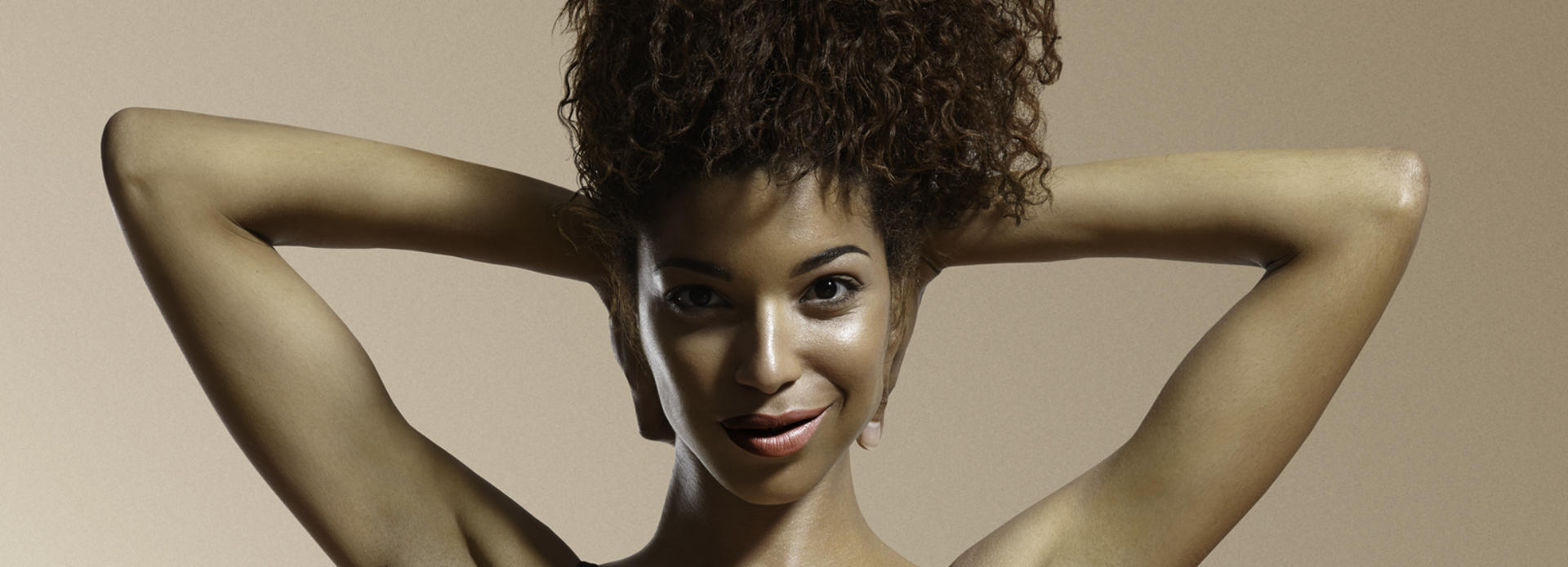 Youthful face of a happy Afro-American woman with radiant skin after hydro dermalinfusion treatment.