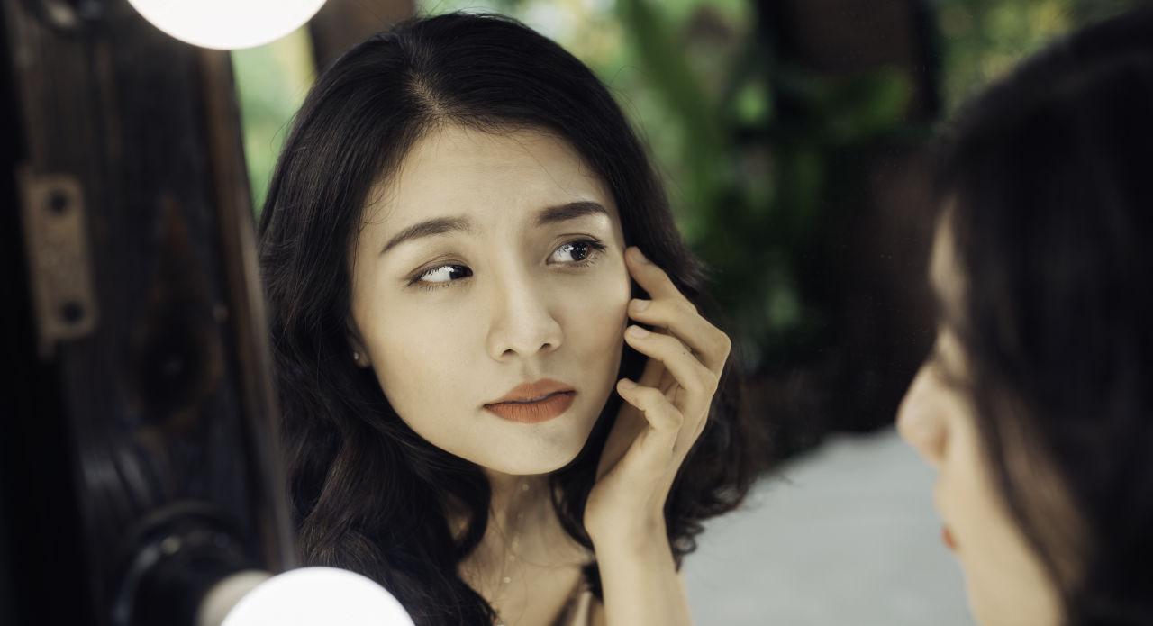 beautiful asian girl looks in the mirror